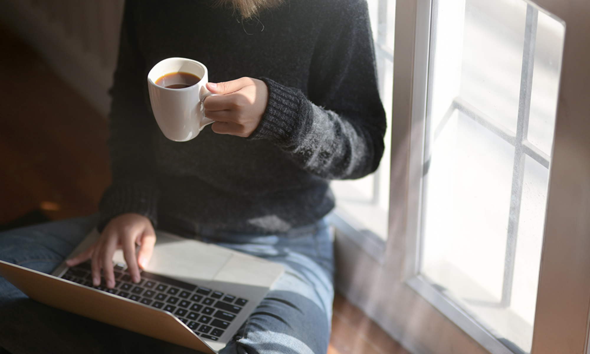 woman-using-laptop-while-holding-a-cup-of-coffee-3759083